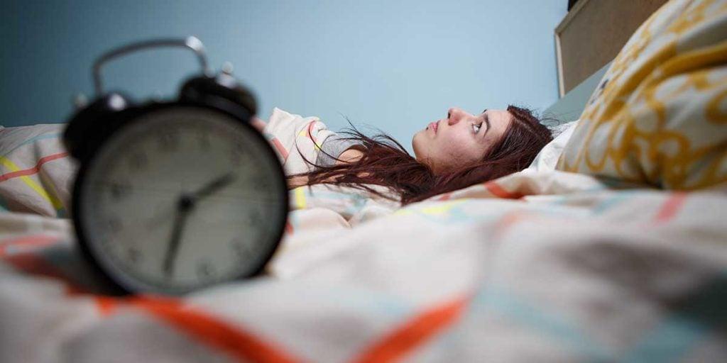 Frau die im Bett liegt - Schlafstörung