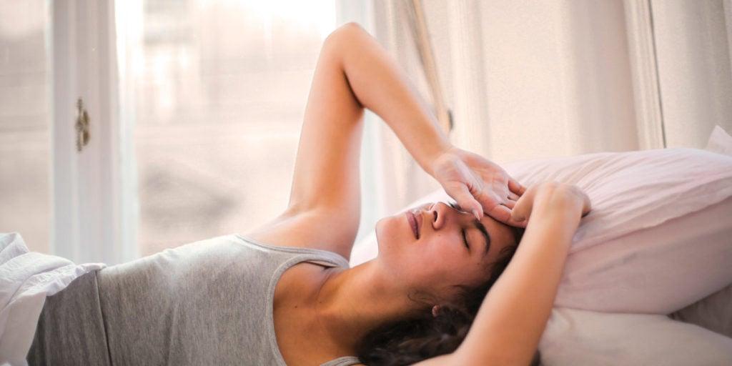 Frau im Bett mit Kopfschmerzen